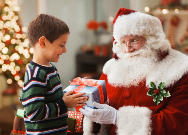 Santa giving Caucasian boy Christmas gift