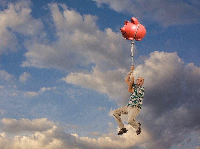 Caucasian man clinging to floating piggy bank